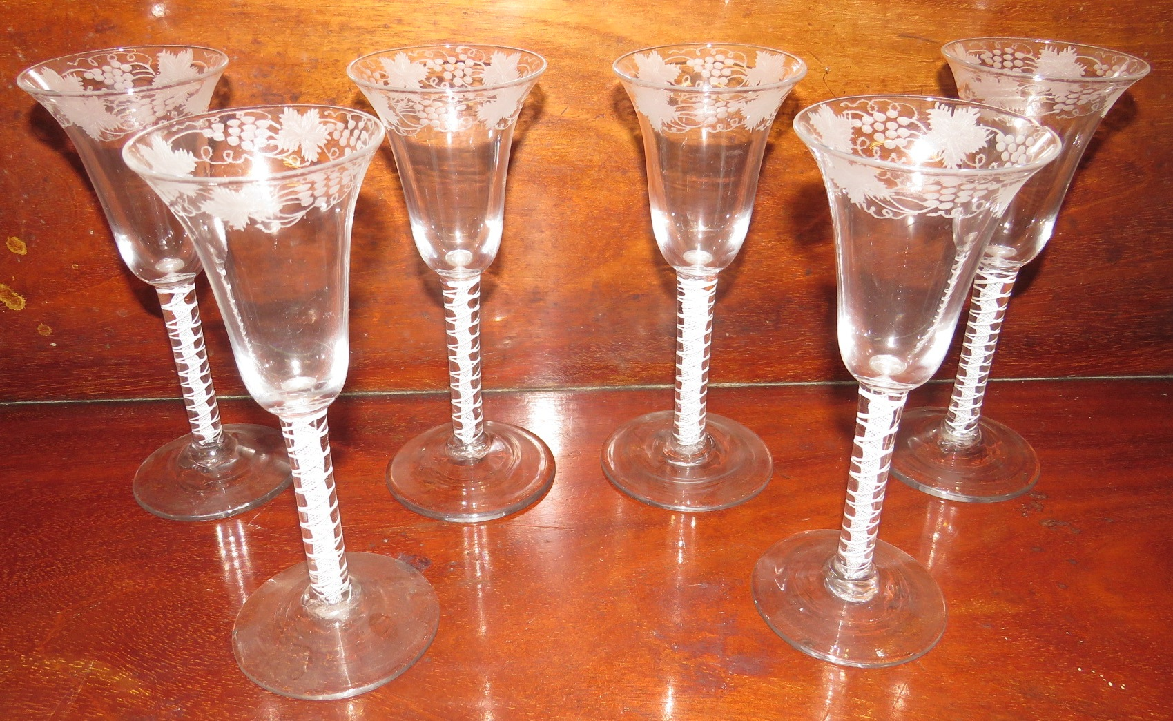 Lot 116 - Six 19th century wine glasses with multi-strand air twist stems, bell-shape bowls etched with border