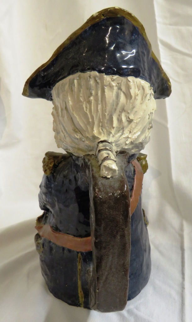 Lot 112 - A large pottery Toby jug glazed and modelled as a seated figure of Nelson with telescope and