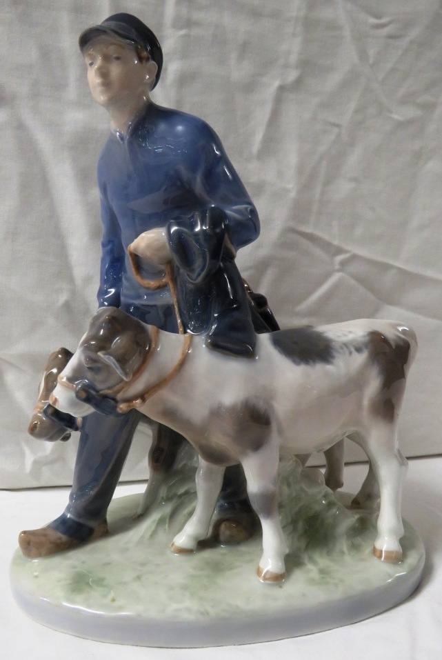 Lot 76 - Royal Copenhagen porcelain figural group of boy leading two calves, on an oval naturalistic base,