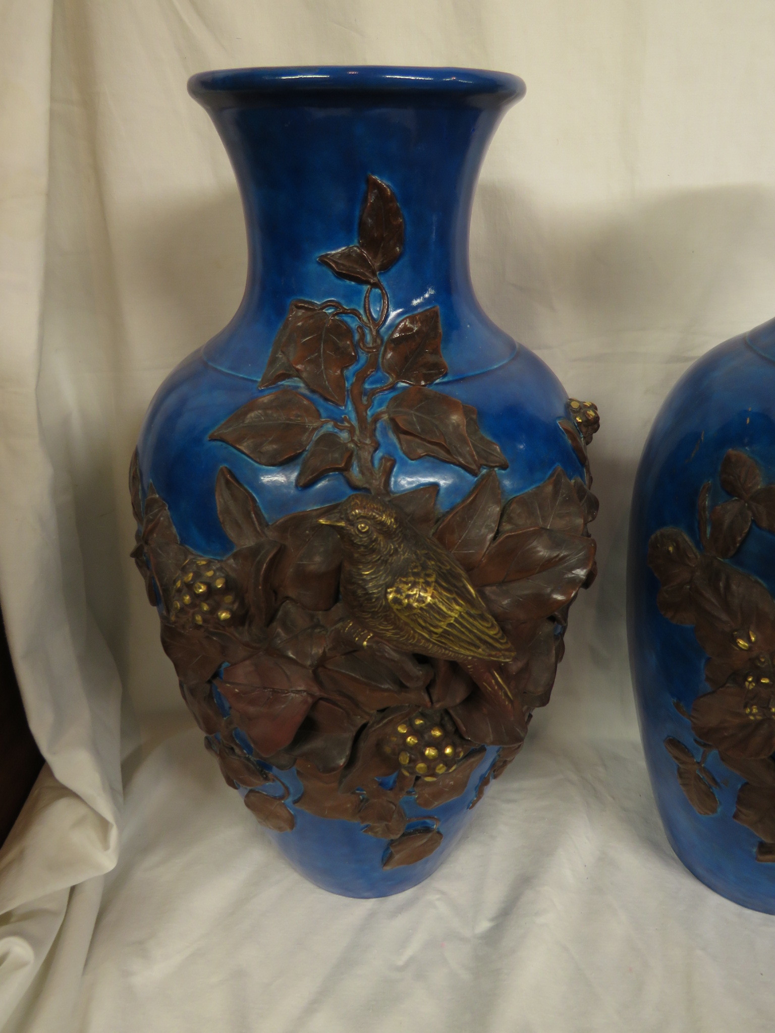 Lot 113 - A pair of blue glazed pottery baluster vases, each with applied decoration of very deeply moulded