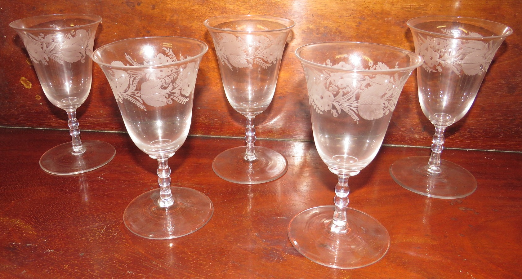 Lot 117 - Five 19th century wine glasses with bell-shape bowls etched with a band of flowers and leaves, the