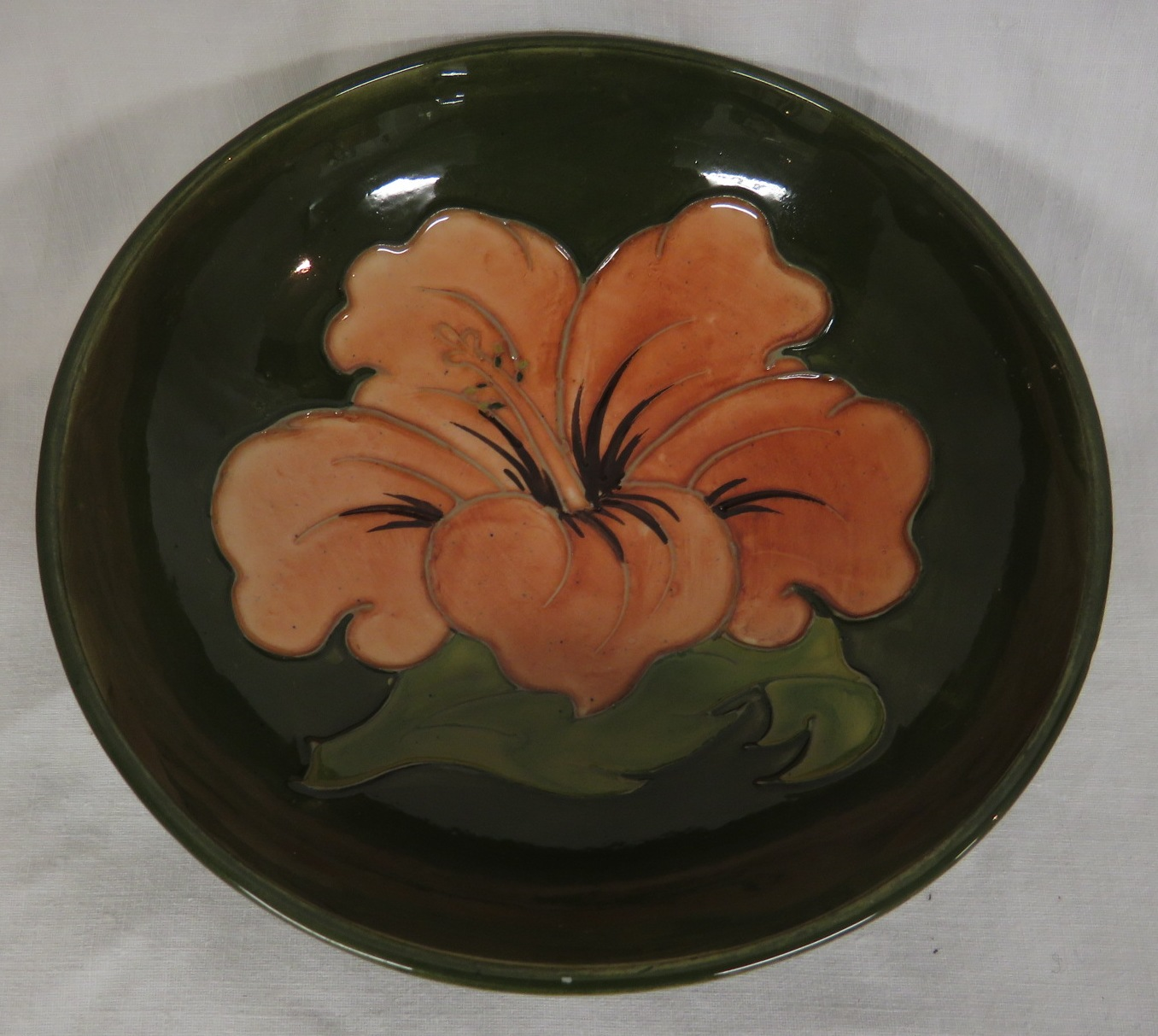 Lot 93 - Moorcroft pottery hibiscus bowl, green ground with pink flower, height 5cm, diameter 14cm, the