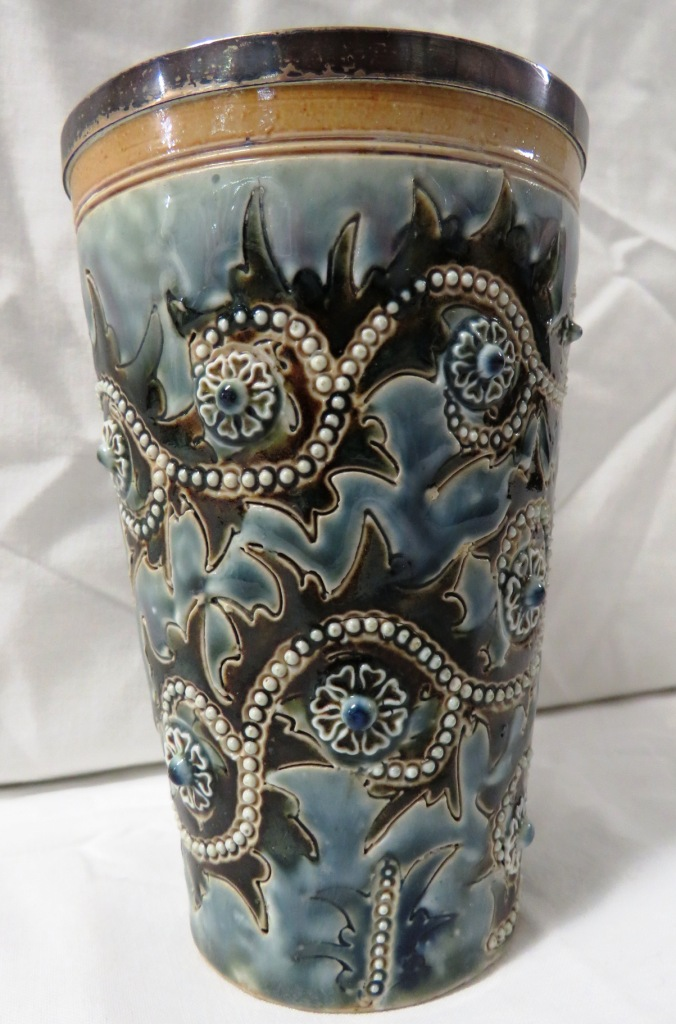 Lot 80 - Doulton Lambeth stoneware beaker with silver rim, glazed in blues and greens with scrolled flowers