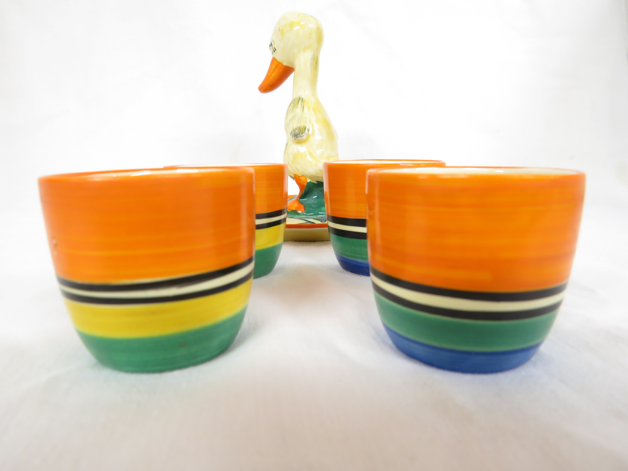 Lot 68 - A Clarice Cliff Bizarre duck egg cruet, the stand with an orange border and stylized leaf pattern in