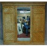 A Victorian pitch pine aesthetic style triple section compactum wardrobe with fitted mirrored