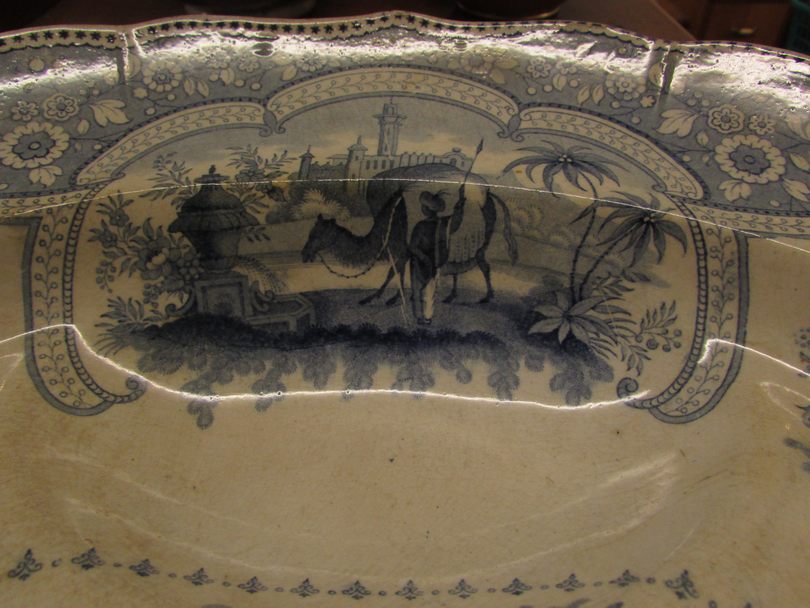 Lot 25 - A large pottery meat or turkey plate, 19th century and transfer decorated in blue on white, the base