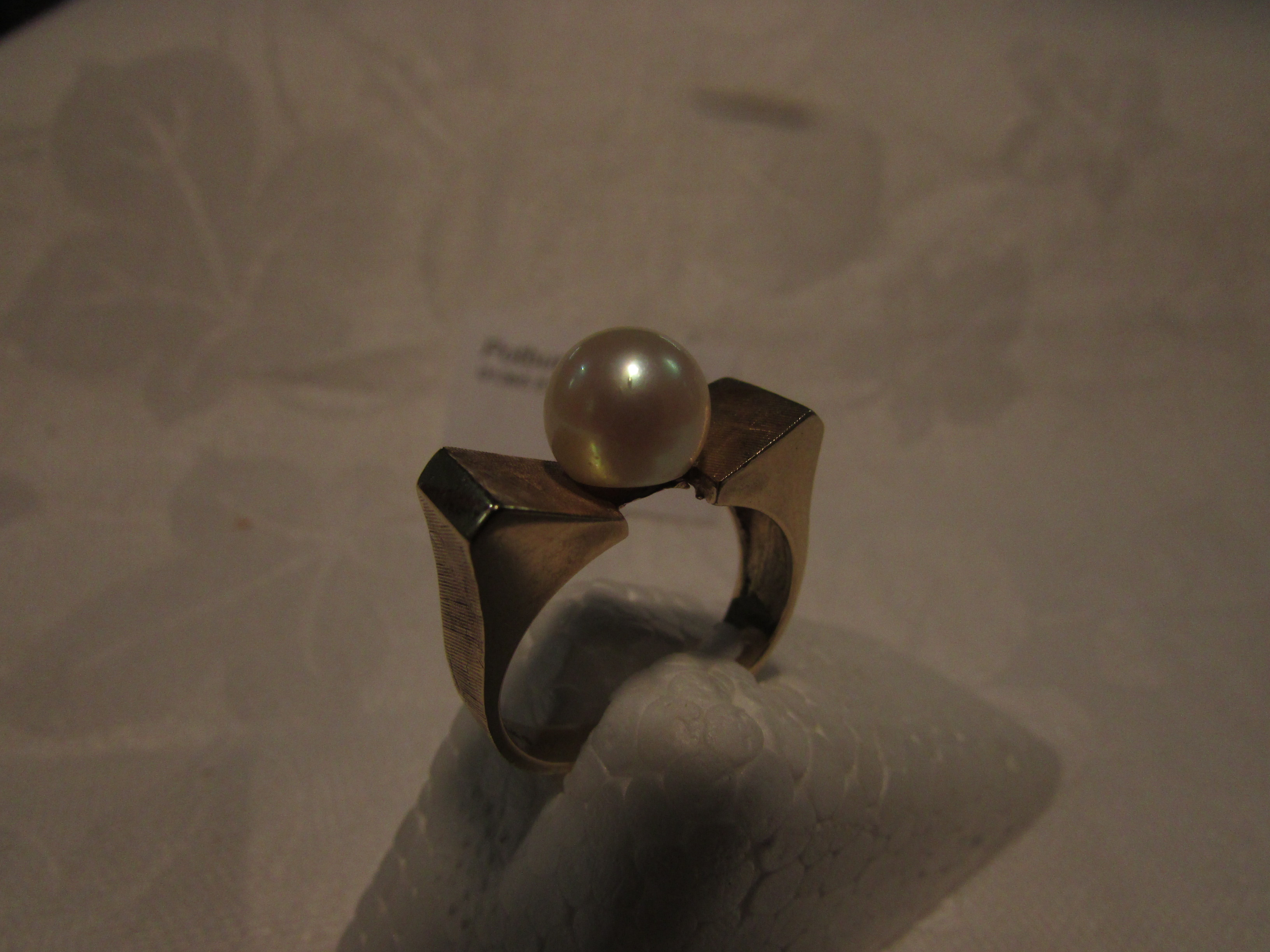 Lot 151 - Gold ring stamped 14K, set with a cultured pearl in an indented setting and machined finish at the