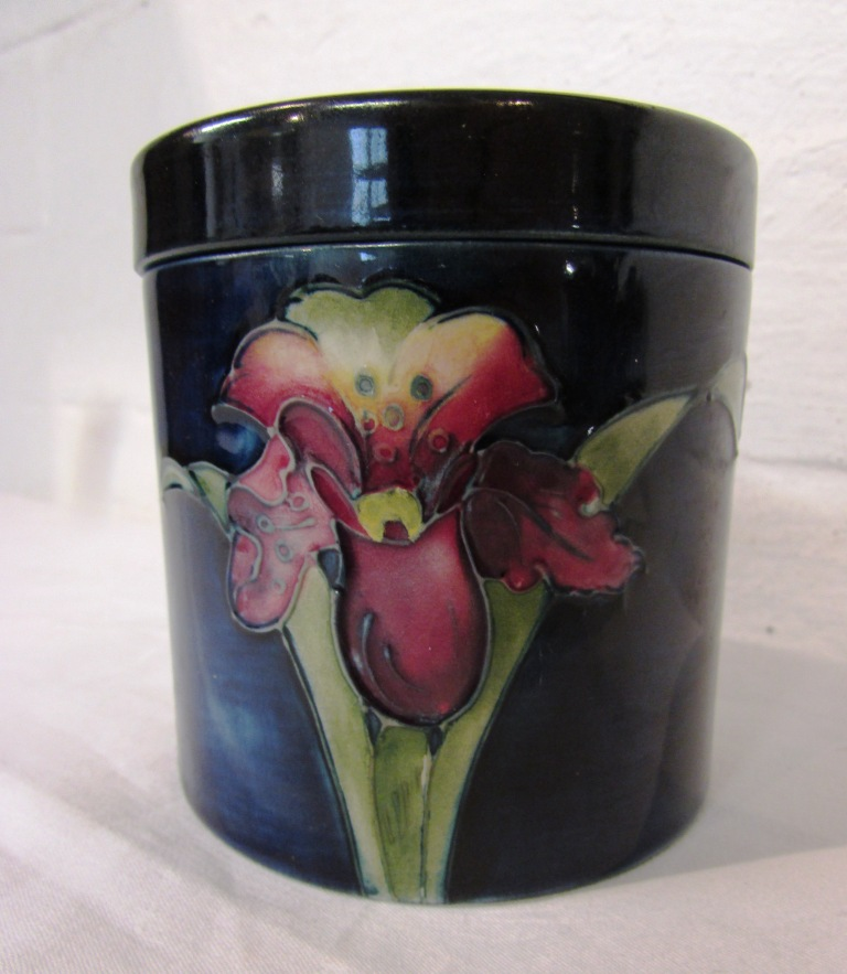 Lot 37 - Moorcroft pottery cylindrical lidded jar, blue ground with red and yellow irises, stamped