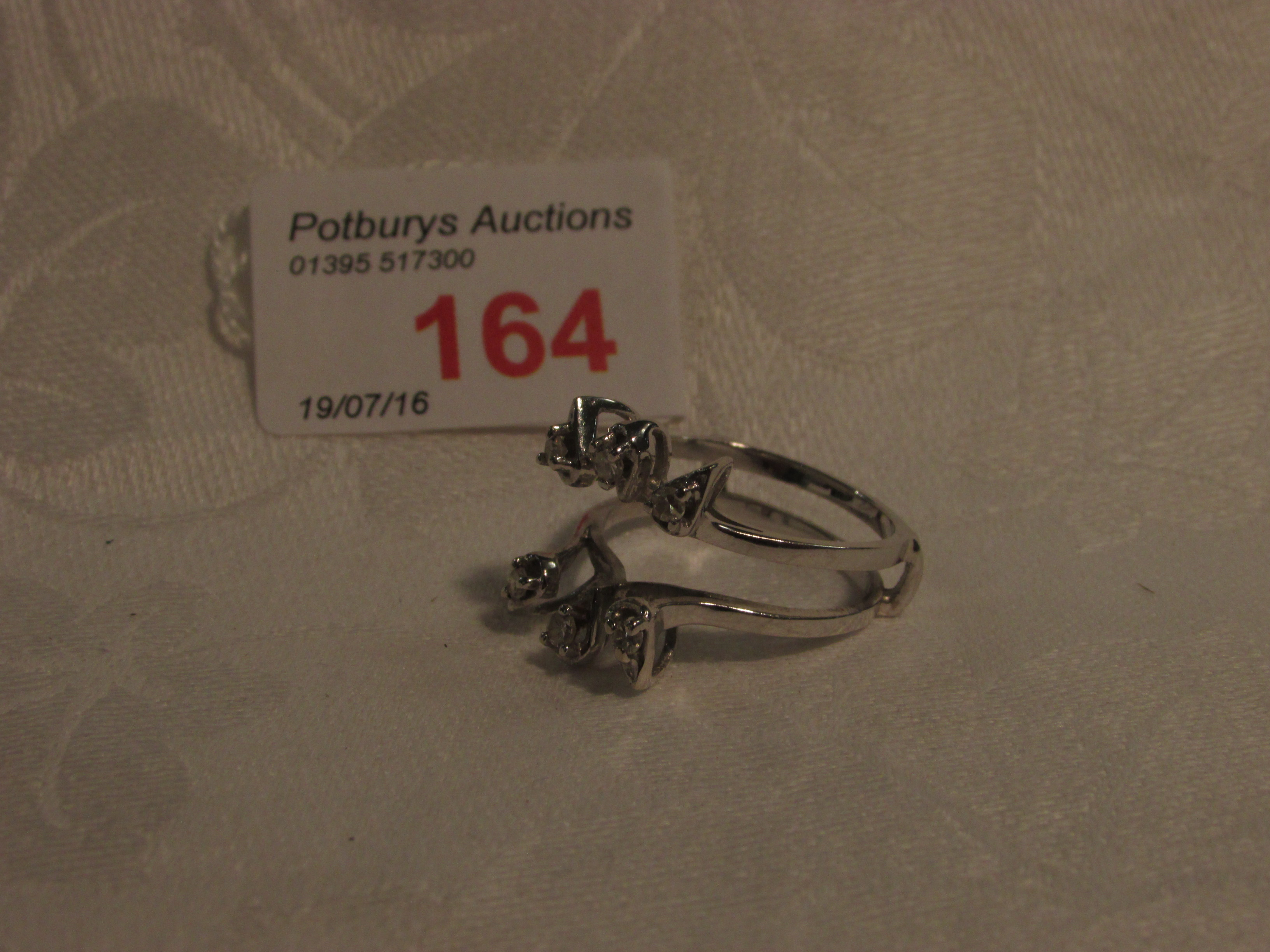 Lot 164 - White gold twin-shank ring stamped 14K and set with a spray of six small brilliant cut diamonds, 4.