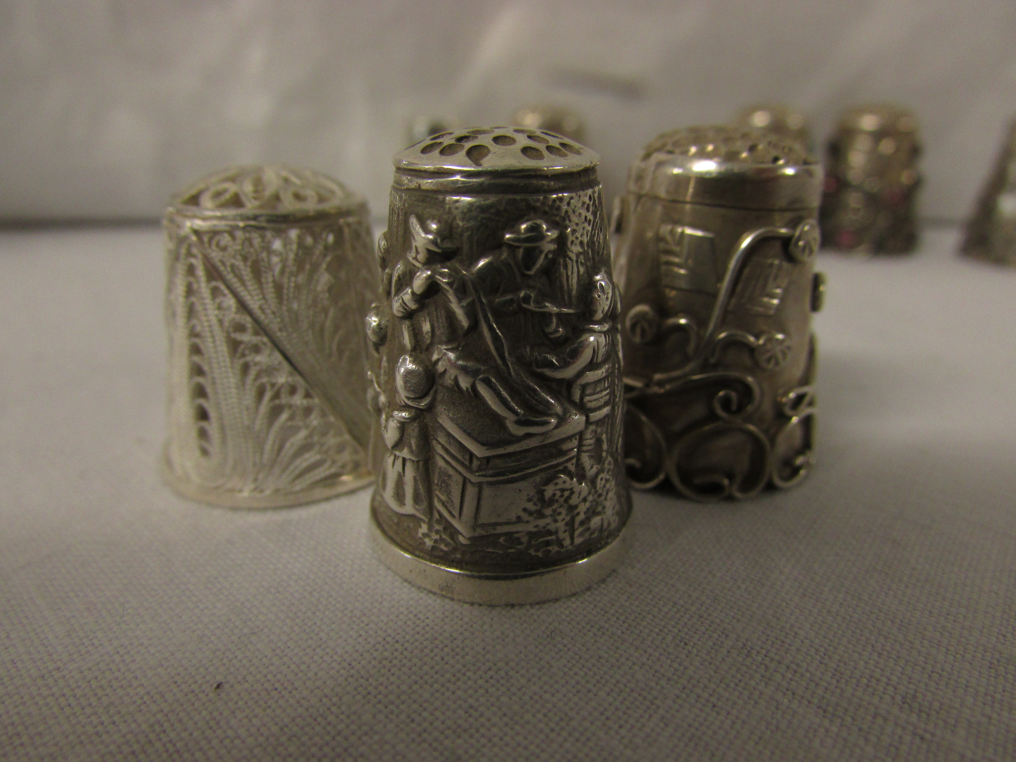 Lot 89 - EIGHT WHITE METAL THIMBLES - one plain stamped 925, three with applied coloured stones and stamped