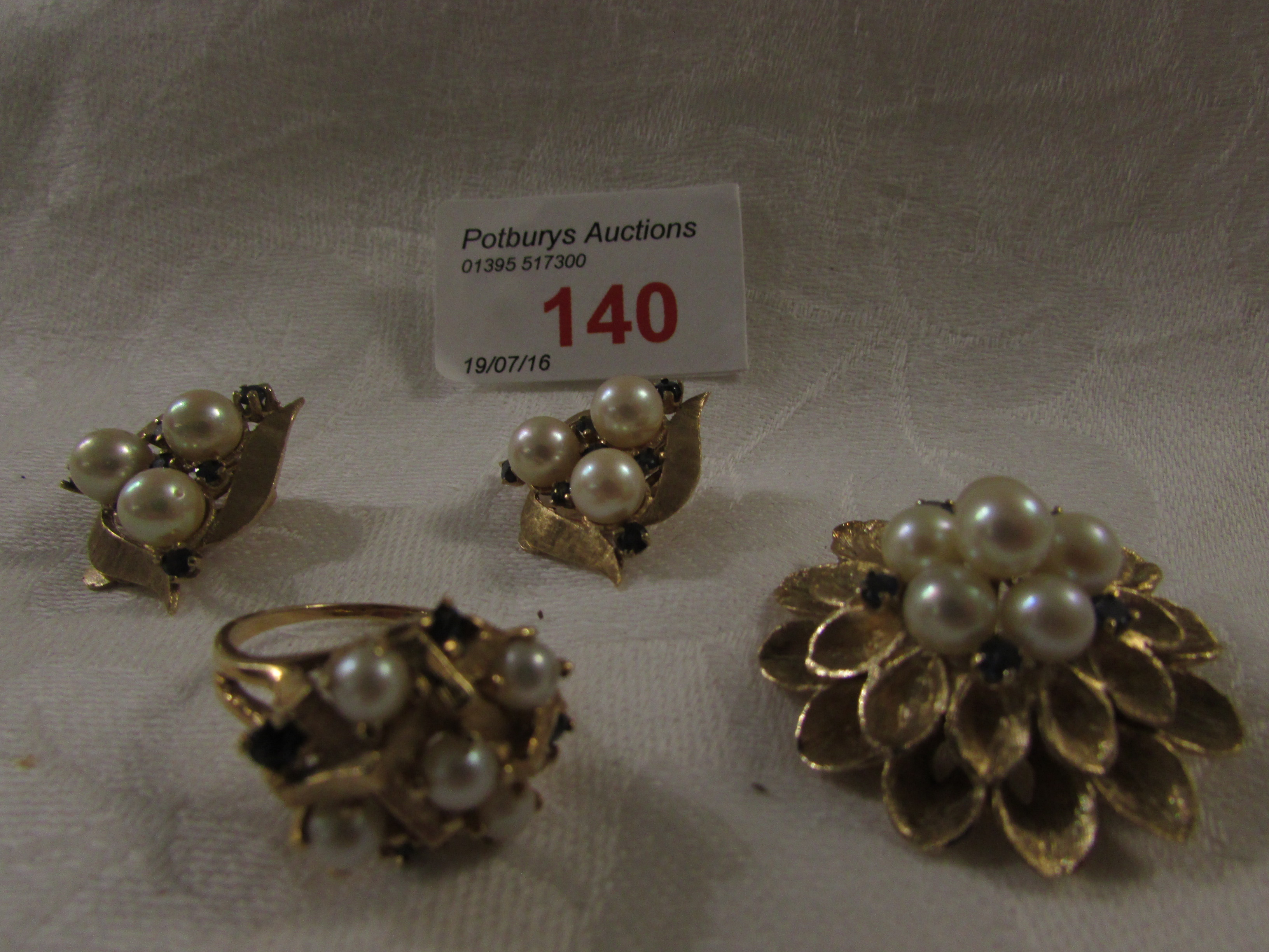 Lot 140 - A gold floret brooch (diameter 3.3cm) stamped 14K set with six cultured pearls and five small blue