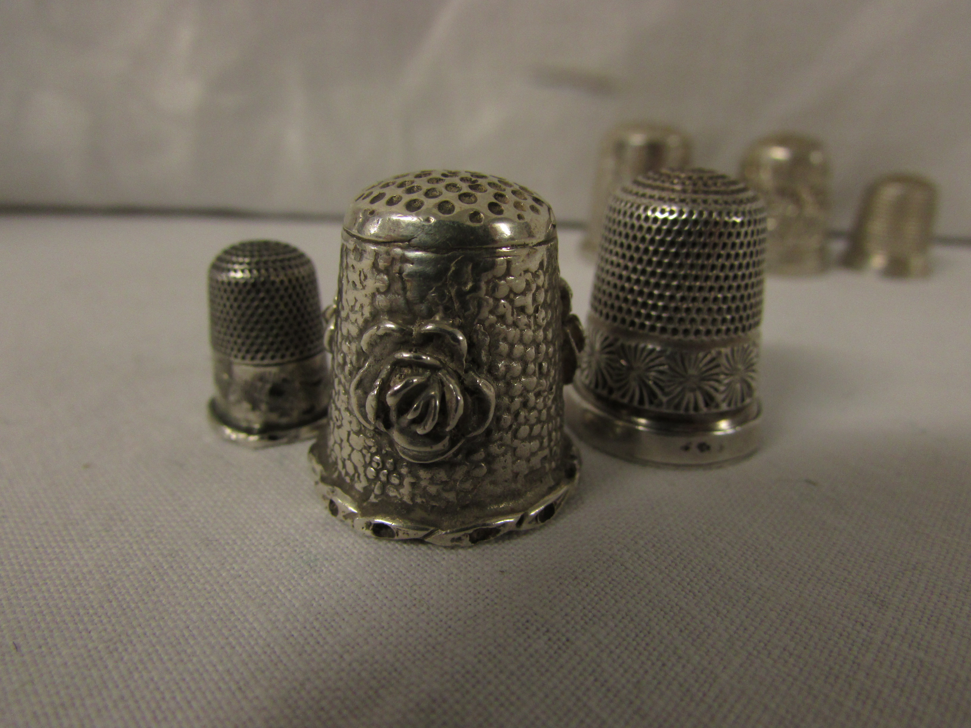 Lot 90 - SIX METAL THIMBLES - a child's with basic chased decoration and no assay marks (1.7cm), one small