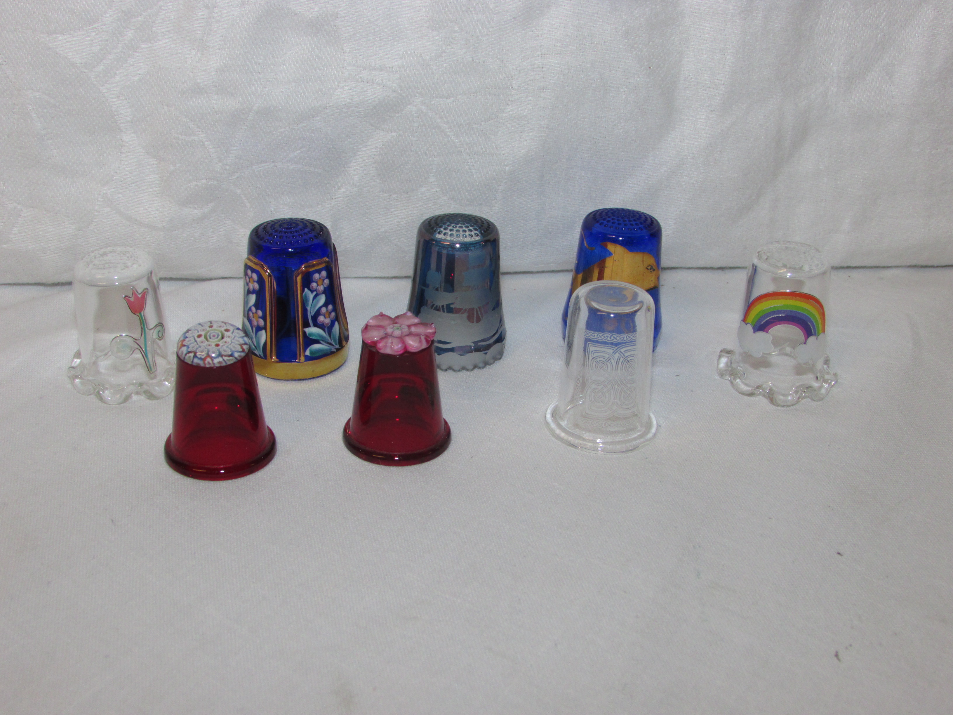 Lot 81 - EIGHT GLASS THIMBLES - two red glass with cane work ends, three blue glass, and three clear glass