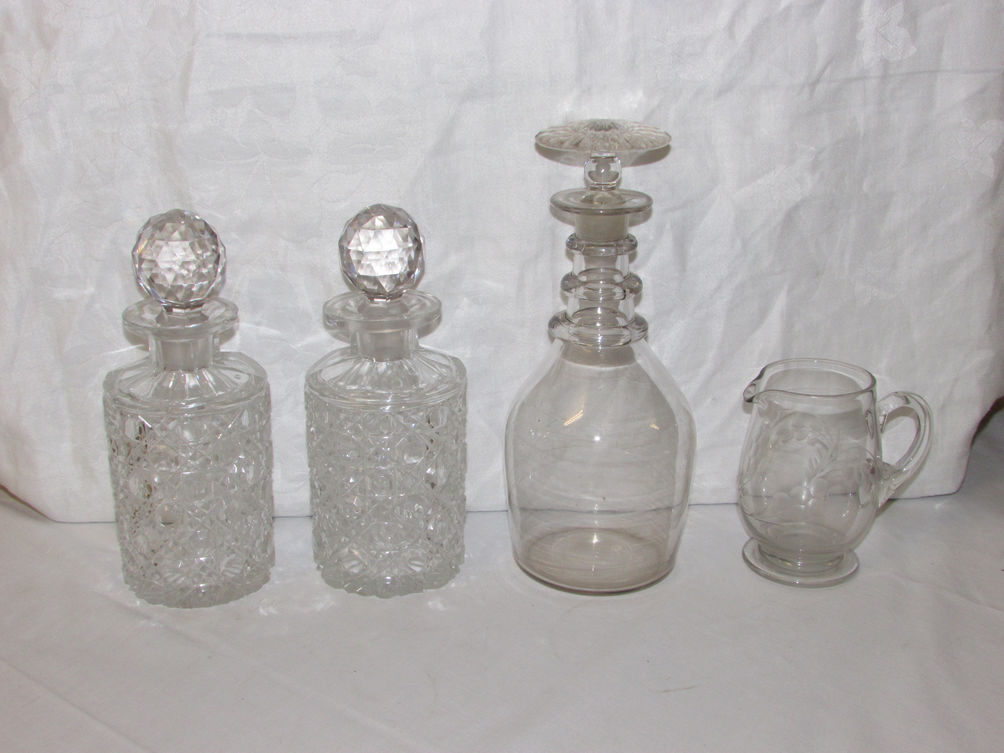 Lot 68 - Two heavily cut glass spirit decanters and stoppers, engraved glass milk jug and wine decanter