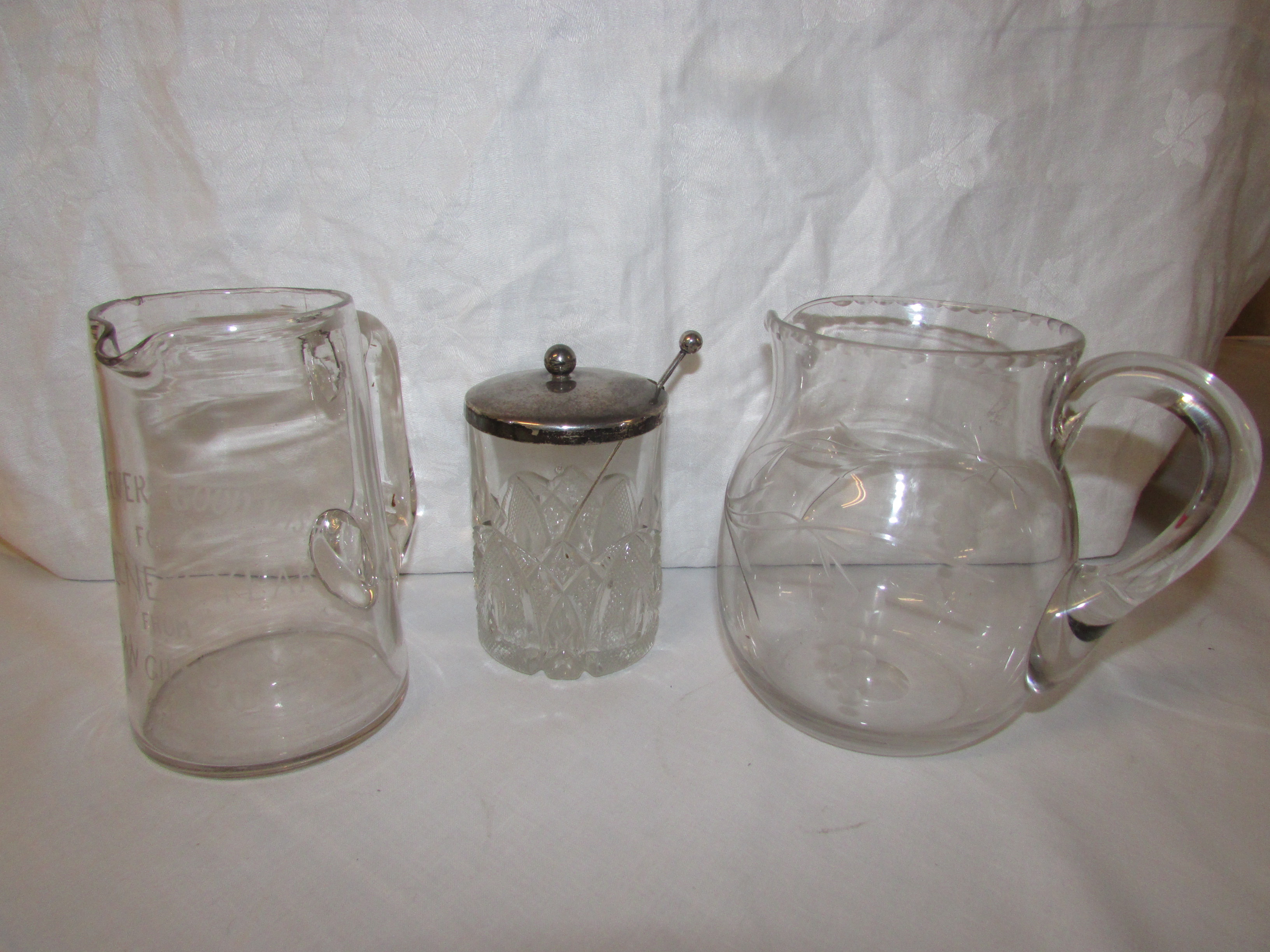 Lot 67 - A glass cream jug engraved with stemmed berries, a glass tankard engraved 'with every good wish
