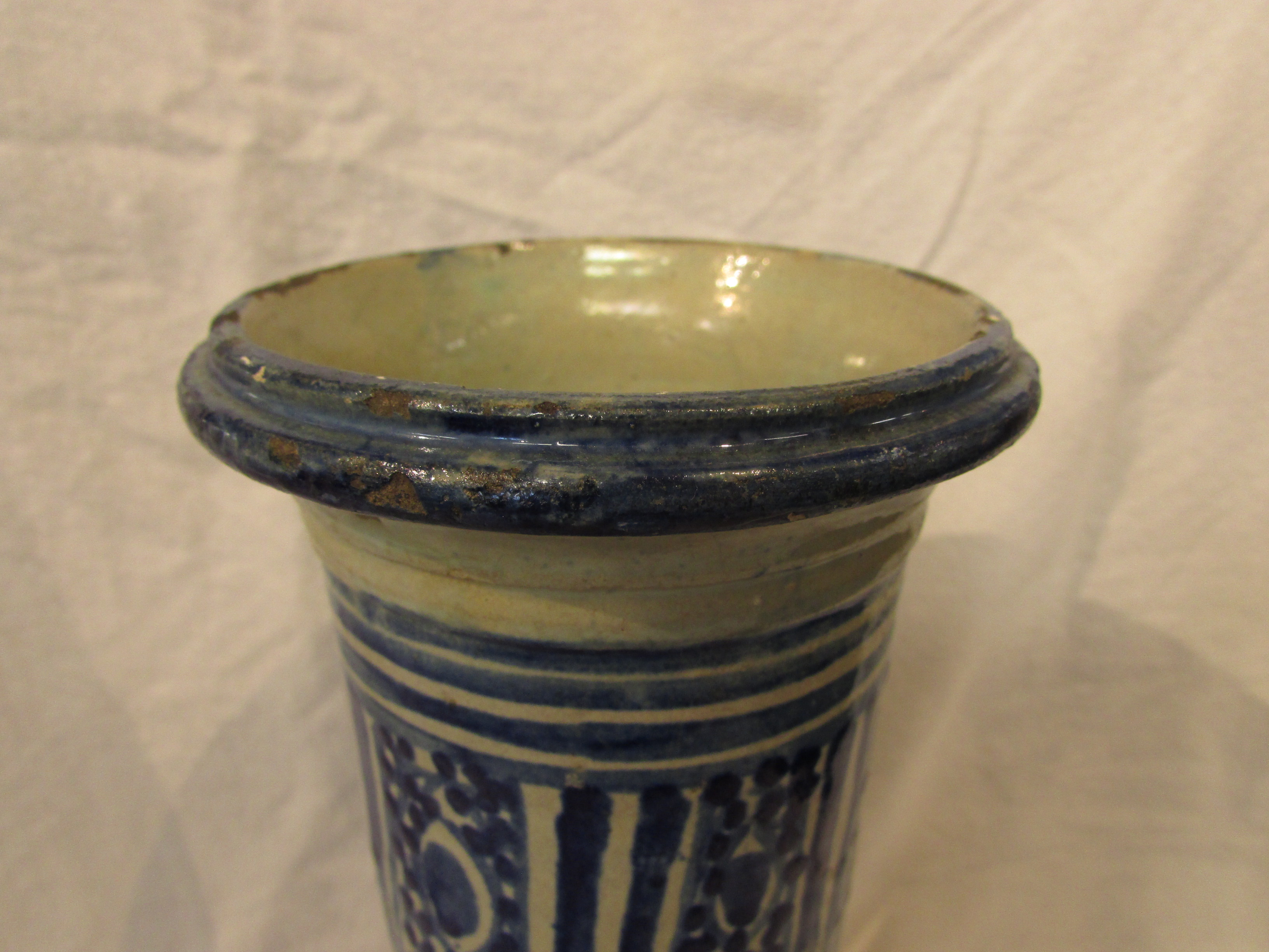 Lot 42 - A pottery cylinder of waisted form and open to both ends, glazed in blue on white with a stylized
