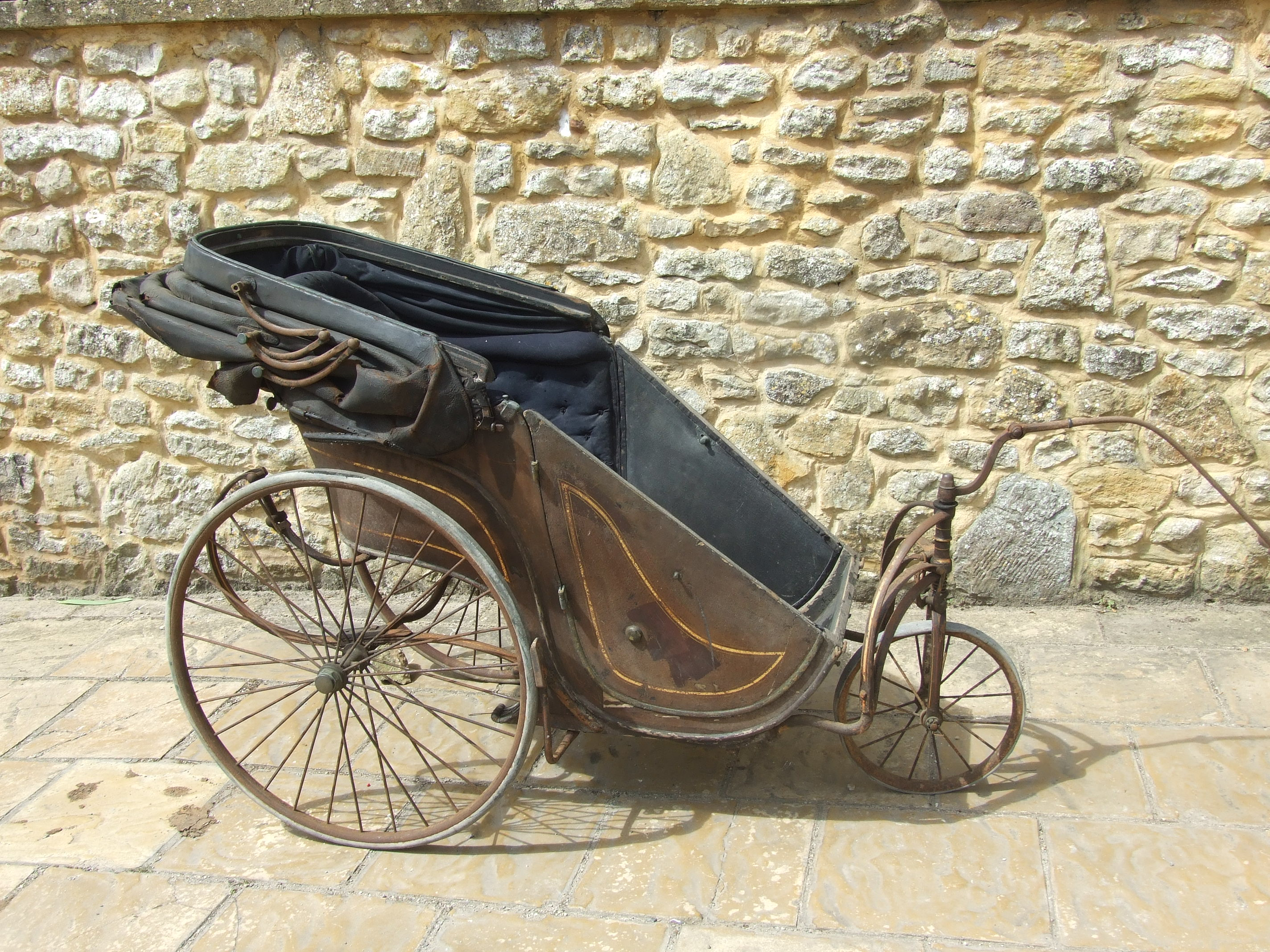A Victorian bath chair with tilter steering and pram hood for