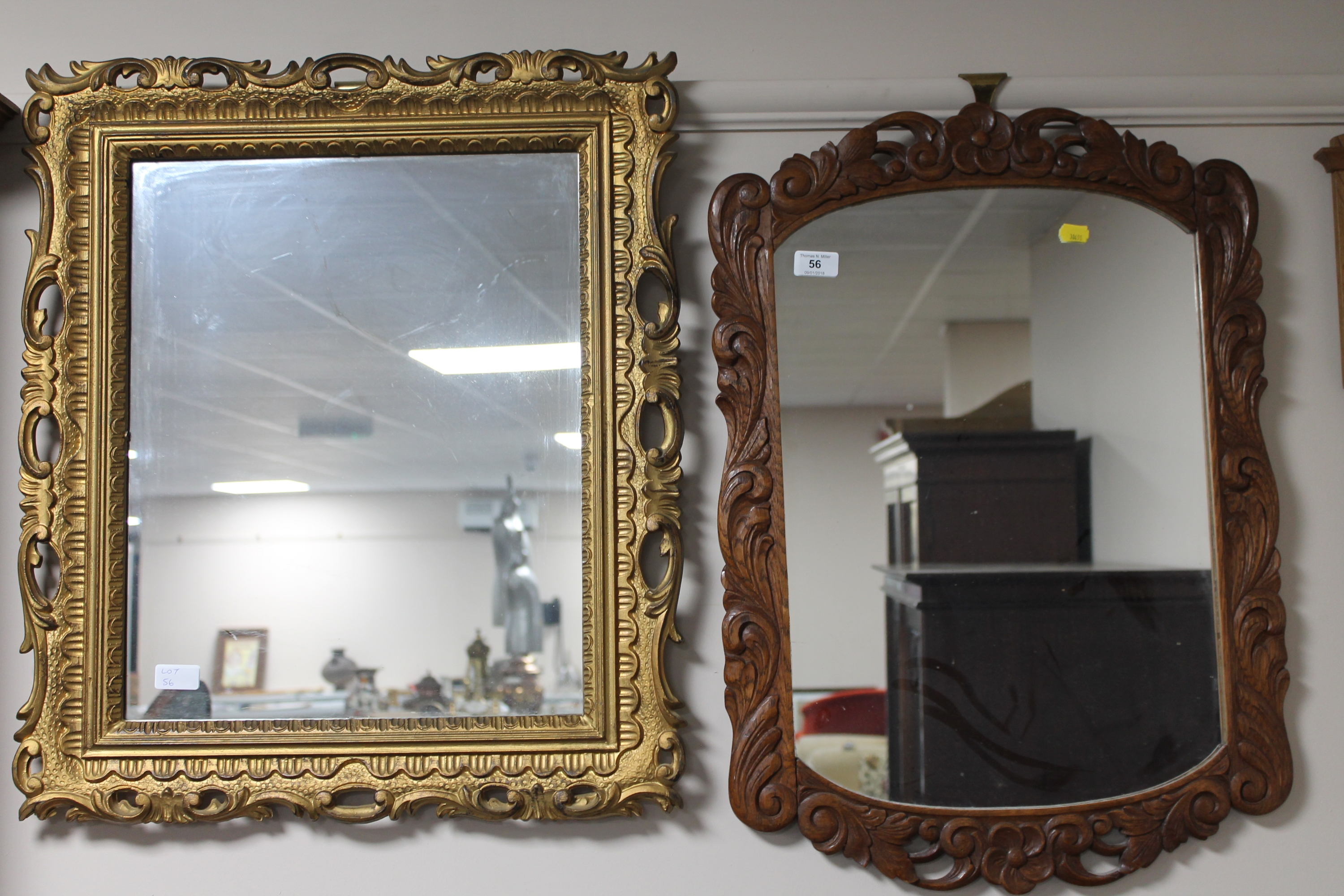 Lot 56 - A carved oak framed wall mirror together with a decorative gilt framed mirror