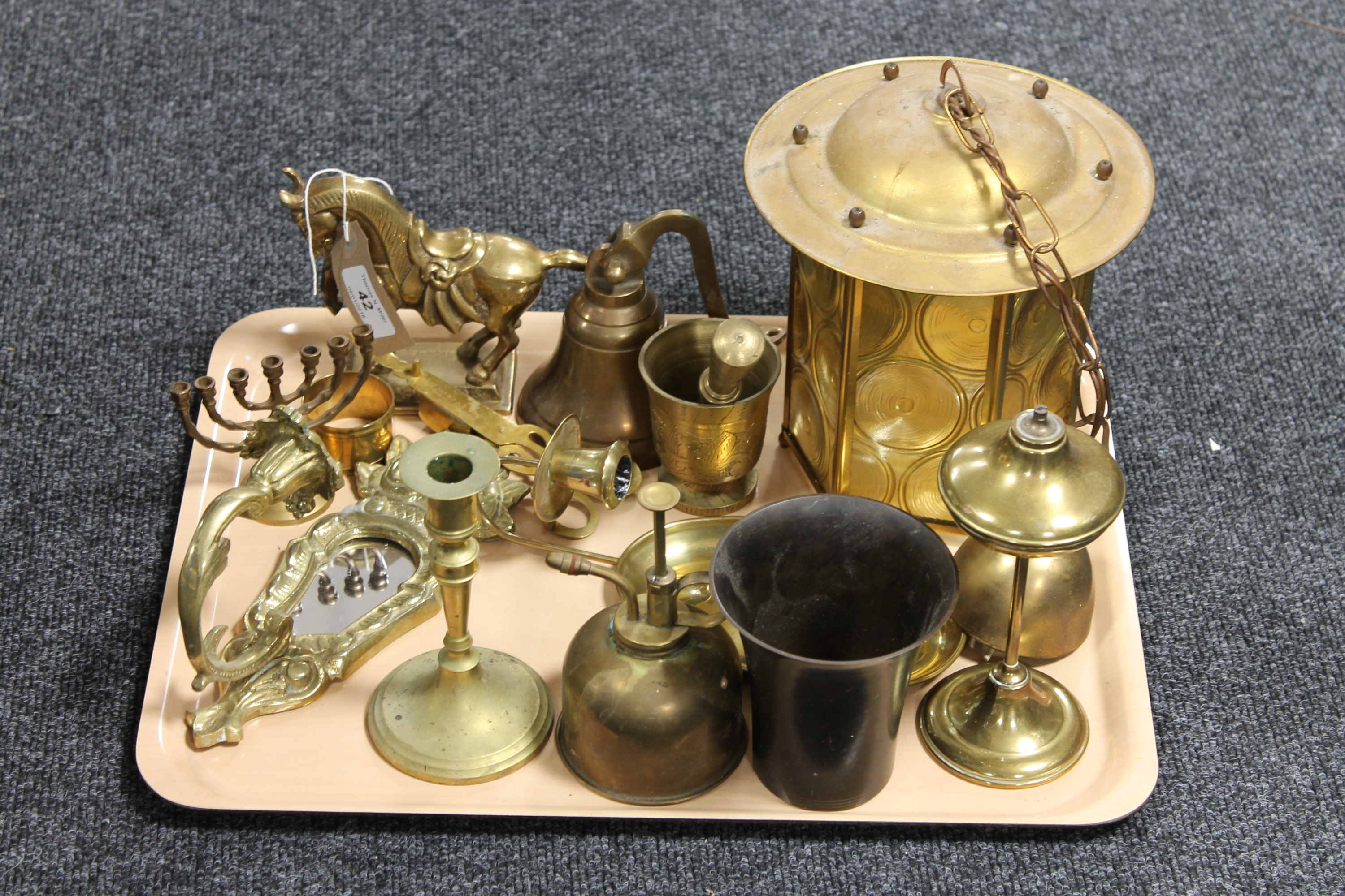 Lot 42 - A tray of brass ware - bell, oil lamp, pestle and mortar,
