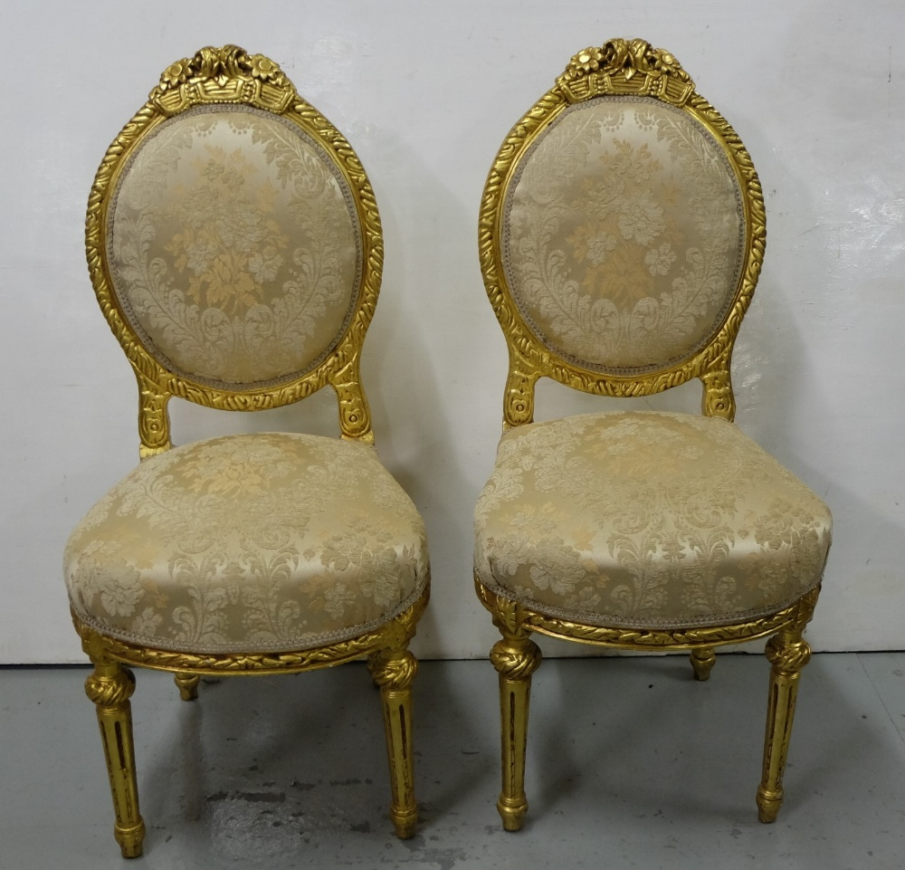 Lot 19 - Matching Pair of carved Gilt Side Chairs, the oval backs mounted with foliate carvings, turned legs,