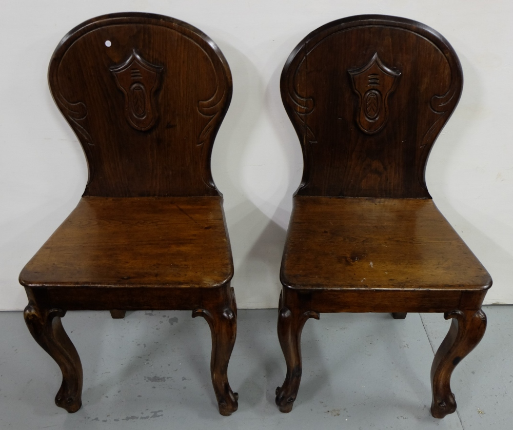 Lot 9 - Matching pair pitch pine, mahogany finish hall chairs with cabriole front legs and crested backs (