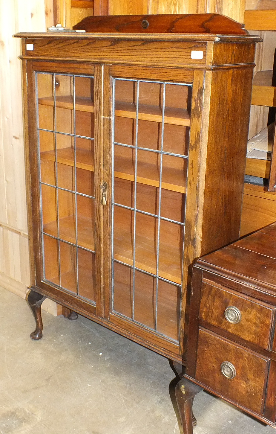 Lot 8 - An oak bookcase, the rectangular top above a pair of leaded-light doors, on cabriole legs, 92cm