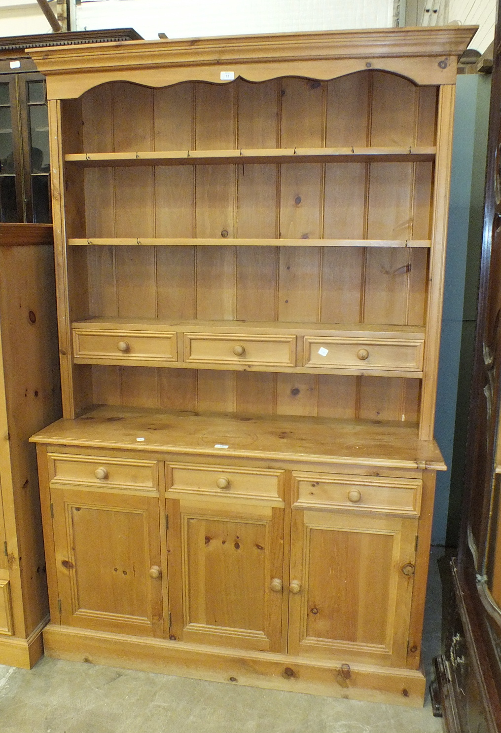 Lot 32 - A modern pine dresser, the open shelves with three drawers above a base fitted with three drawers