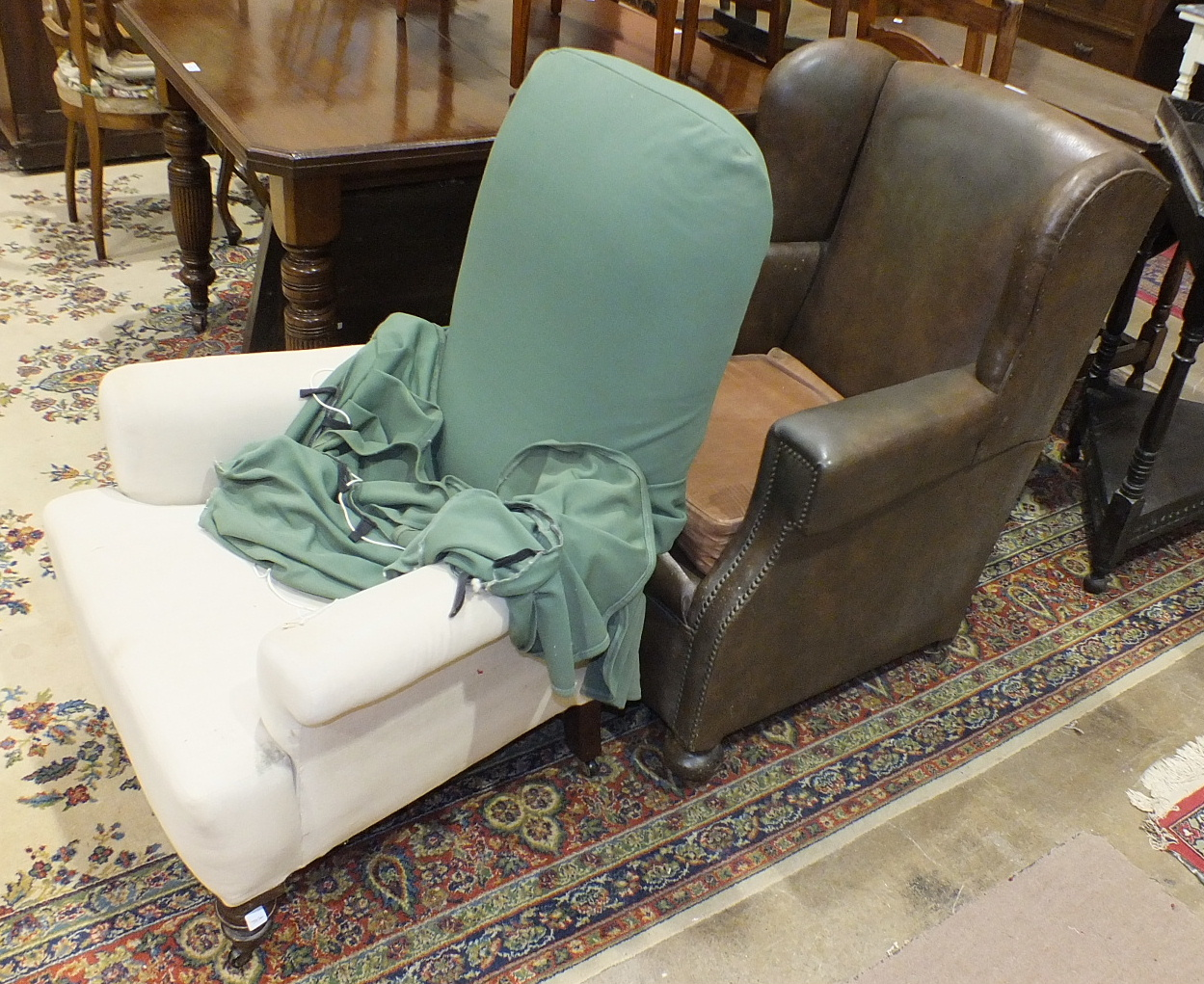 Lot 9 - A Victorian upholstered salon chair on turned walnut feet and a Rexine-covered wing armchair, (2).