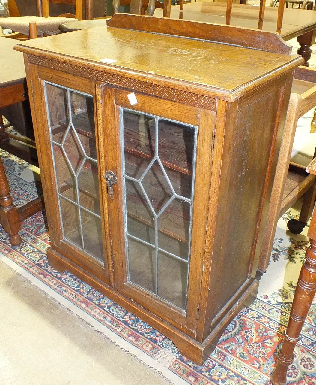 Lot 33 - An oak low bookcase fitted with a pair of leaded-light doors, 70cm wide, 92cm high, an oak tea