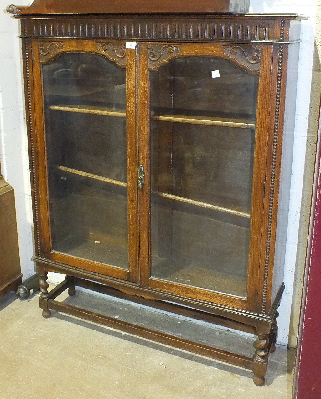 Lot 37 - An oak bookcase, the rectangular top above a pair of glazed doors, on short turned legs united by