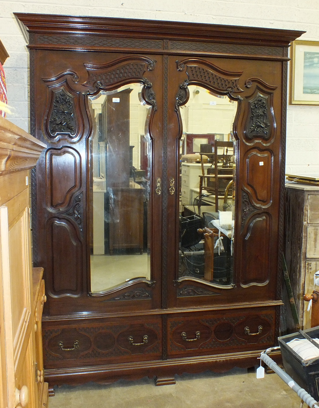 Lot 20 - An Edwardian mahogany carved wardrobe, the cornice above a pair of mirrored doors, on two-drawer
