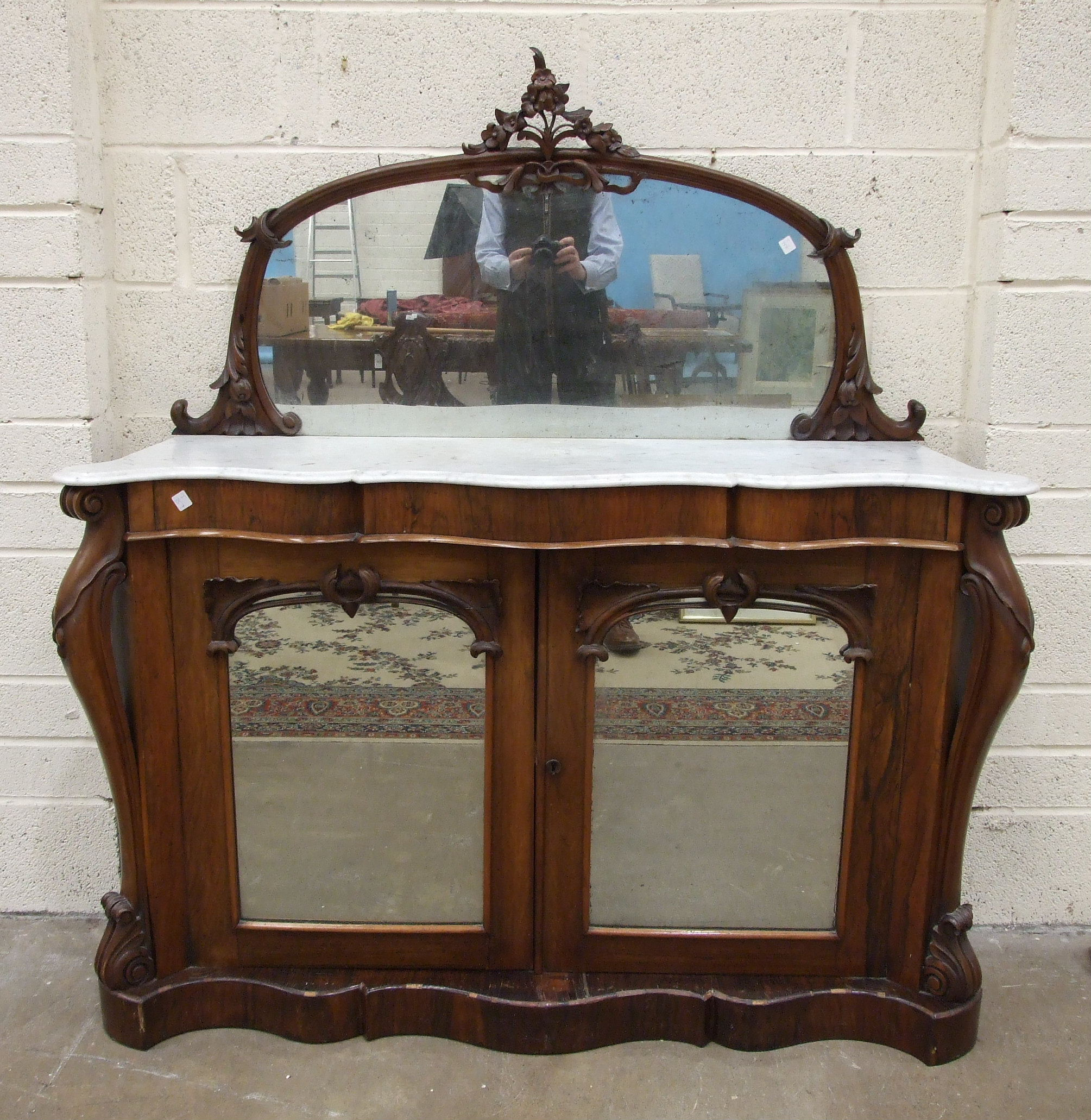 Lot 55 - An early-Victorian rosewood side cabinet, the mirrored back with carved frame above a serpentine