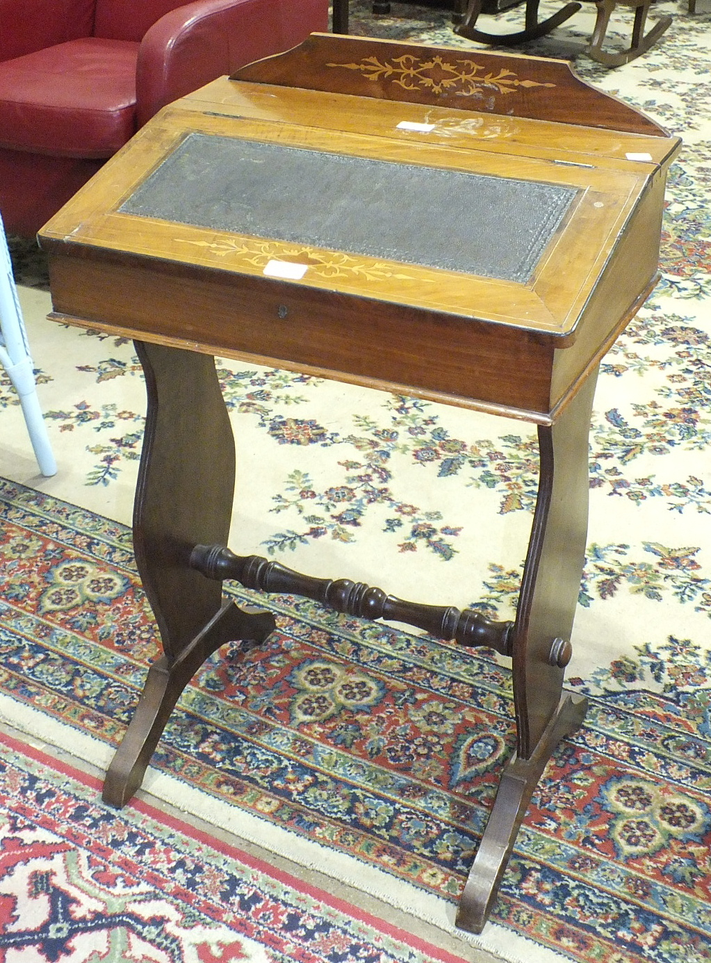 Lot 41 - An Edwardian inlaid mahogany desk, the hinged sloping top above two end supports, 56cm wide, 86cm