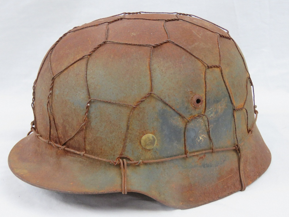 Lot 131 - A WWII German Luftwaffe helmet with camo