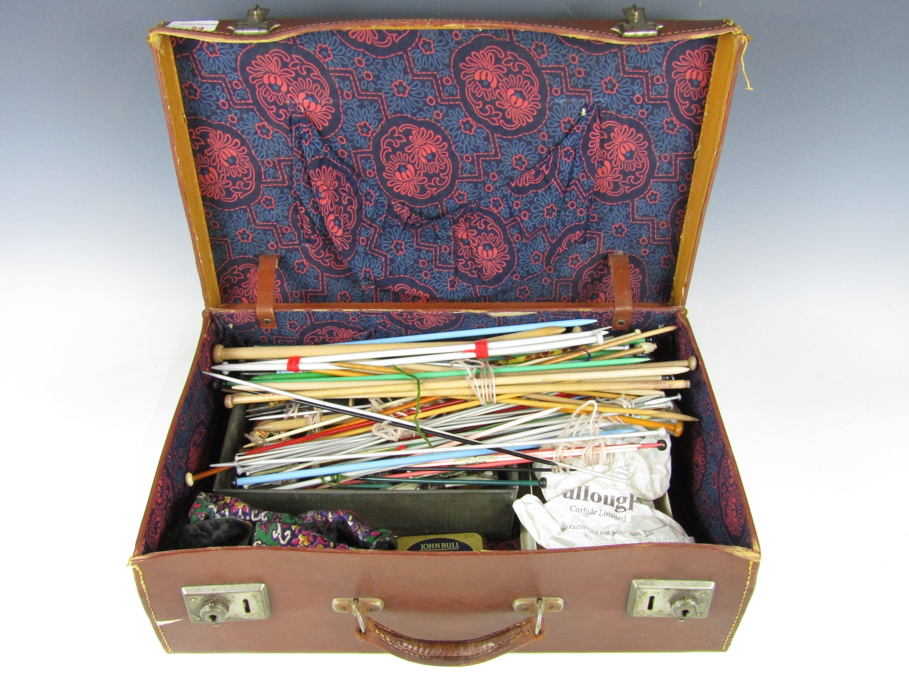 Lot 54 - A vintage hide case containing sundry sewing and knitting accessories