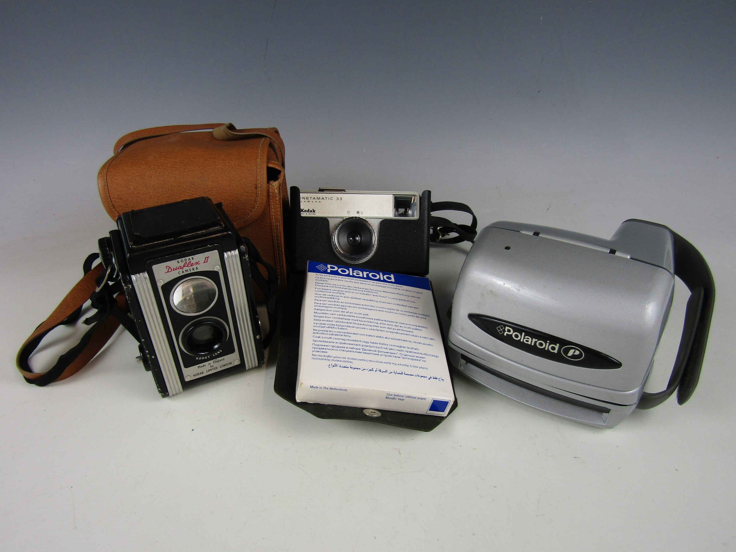 A vintage Polaroid camera together with other cameras