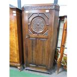 1920's oak hall cabinet with canted reeded sides, carved medallion above linen fold carving to door,