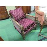 Victorian Bergère armchair with maroon coloured cushions. Estimate £30-50.