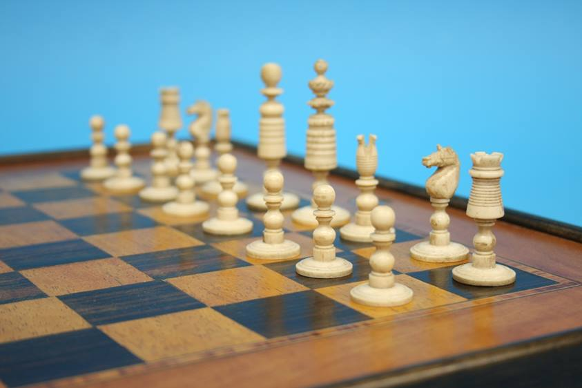 Lot 5 - A stained bone chess set and chess board