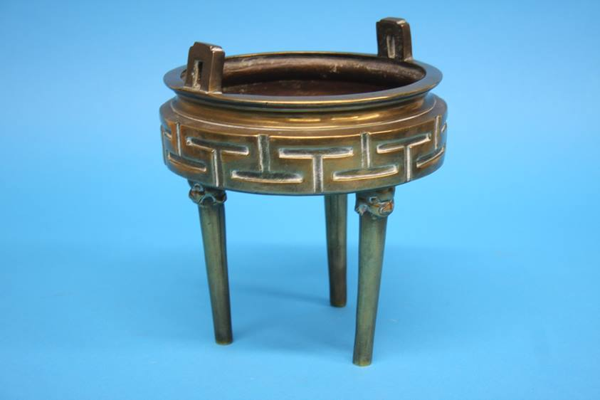 Lot 25 - A bronze tripod censer with lion mask terminals and geometric design. 17 cm diameter by 20 cm high