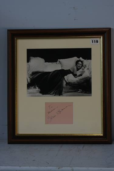 Lot 119 - Gloria Swanson (1899 - 1983), signed page, mounted with black and white photograph of Swanson posing
