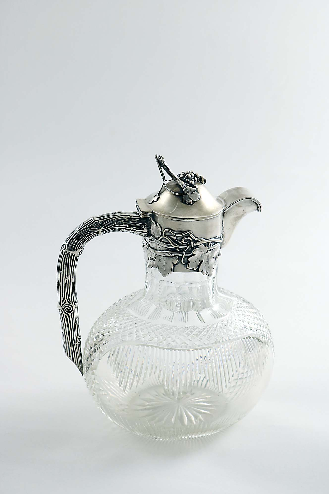Lot 538 - AN EARLY 20TH CENTURY GERMAN MOUNTED CUT-GLASS CLARET JUG with a rounded oval body, a bark-
