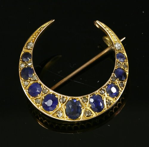 Lot 55 - An Edwardian sapphire and diamond closed crescent brooch,