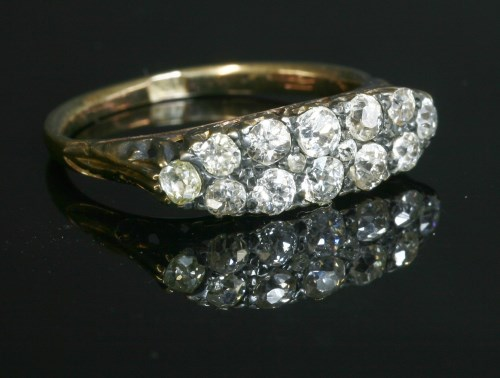 Lot 60 - An Edwardian two row diamond boat shaped carved head ring