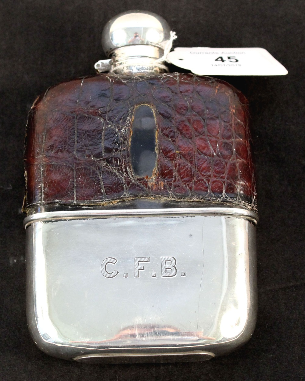A hip flask with silver fittings and cup,