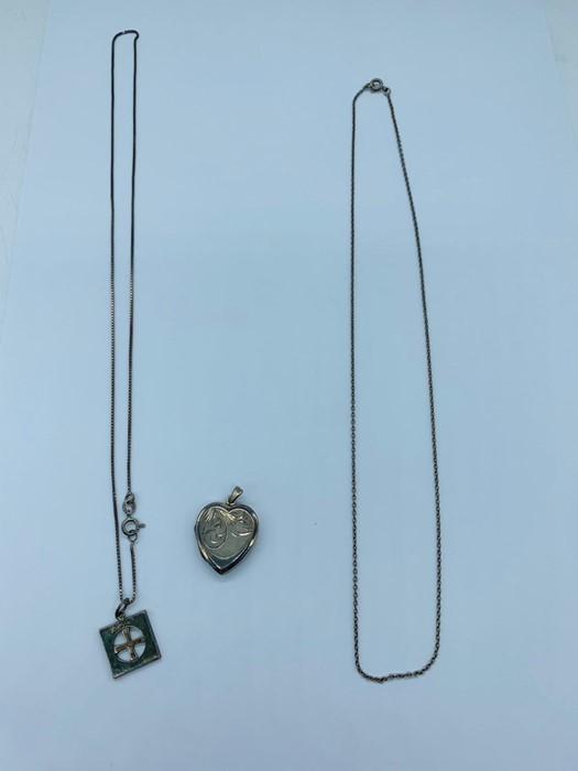 Two silver necklaces and one heart pendent