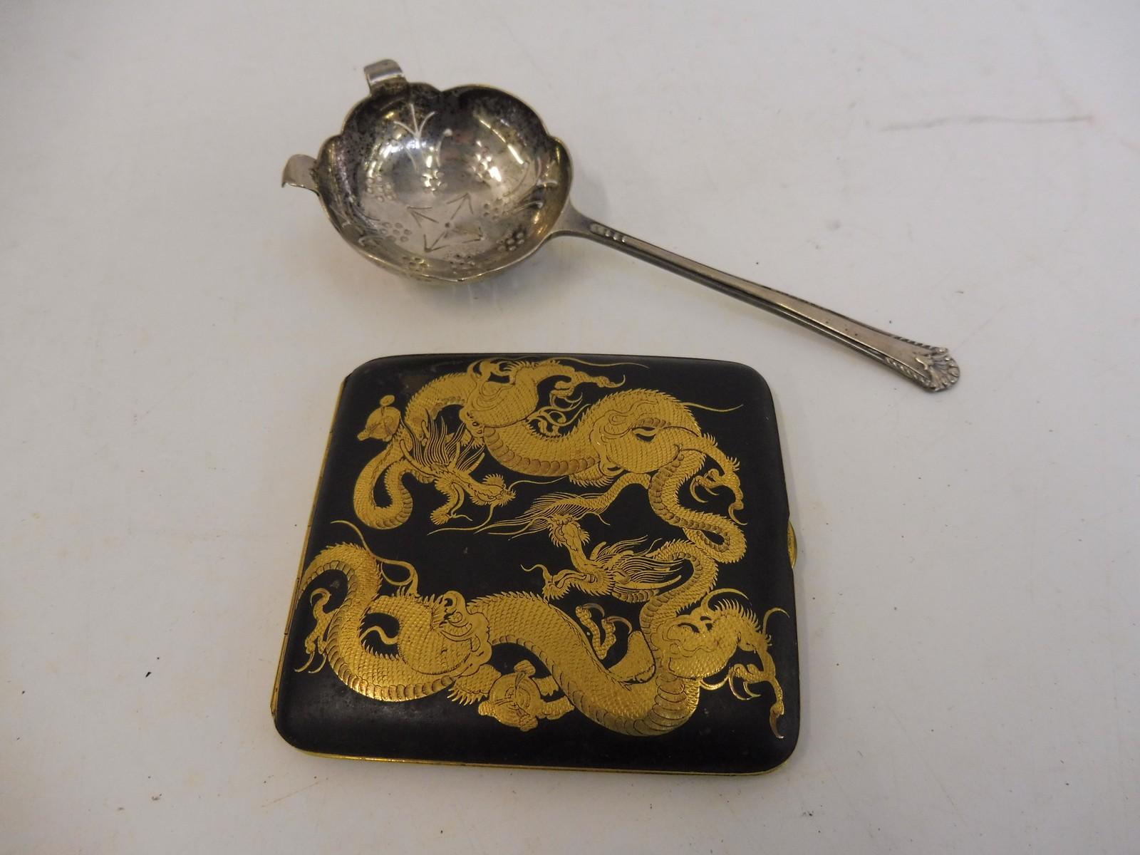 Lot 22 - A silver strainer/sifting spoon and an Oriental lacquered cigarette case.