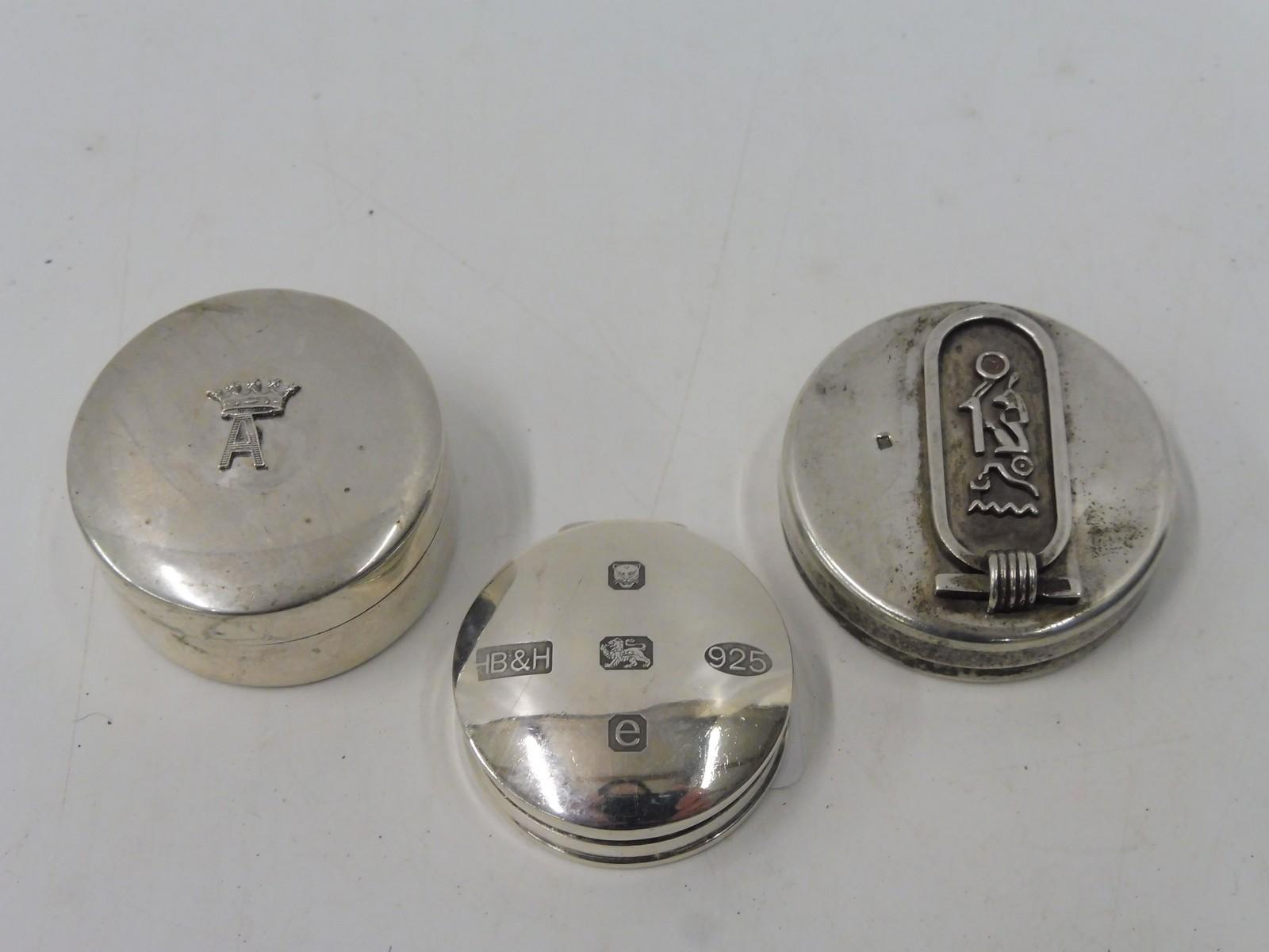 Lot 39 - A small circular silver pill pot, an Italian silver pill pot and an unusual white metal pill pot.