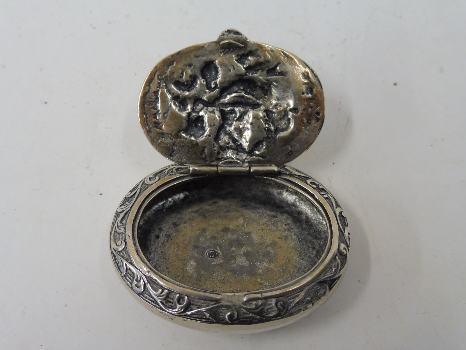 Lot 31 - A Continental silver oval lidded box, the lid with a scene of musicians in deep relief.