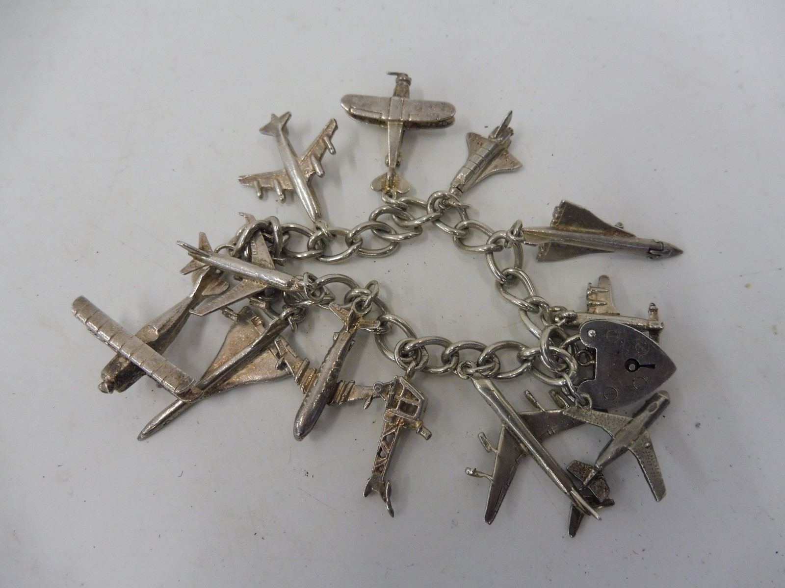 Lot 28 - A silver charm bracelet comprising 12 miniature aeroplanes and a padlock, the charms include